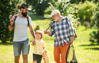 Father and son with grandfather carrying fishing gear