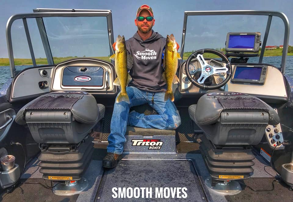 Jason holding two fish next to Smooth Moves boat seat suspension system