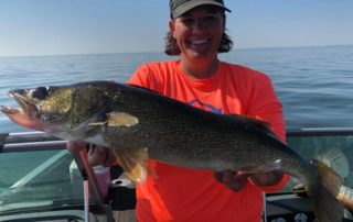 Pro angler Nancy Koep holding fish on boat