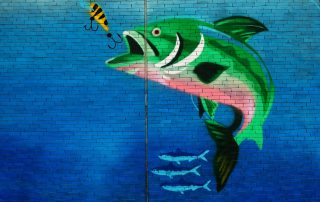 A painting of a fish about to swallow bait on a hook.