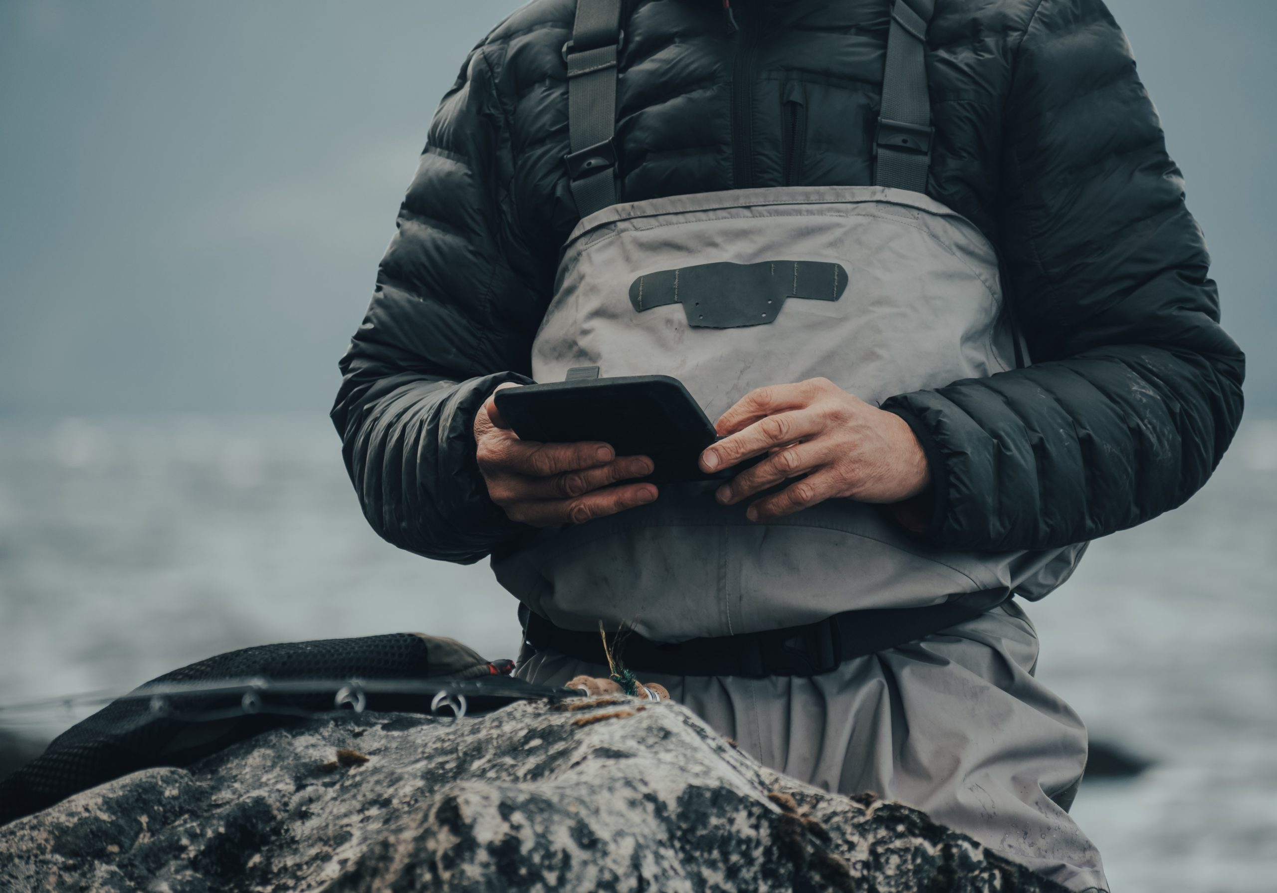 Man holding a gadget while fishing.